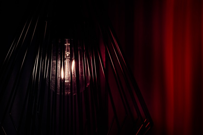 The Black Lodge: abstract light bulb against red curtains